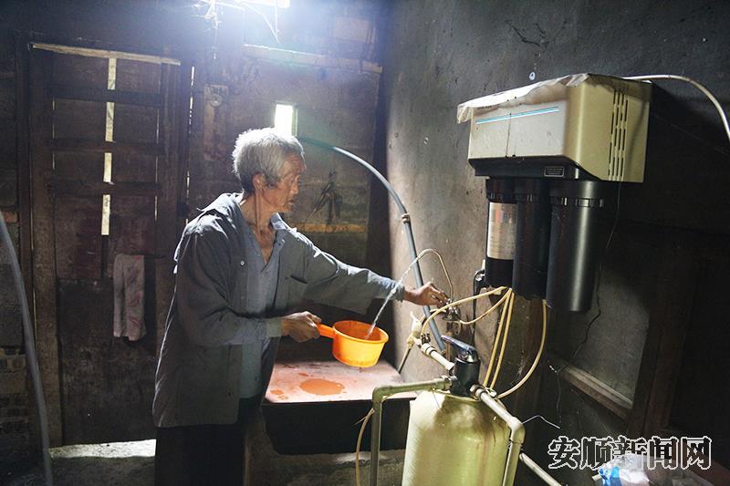 紫云村民梁石堡接净水器的水喝.jpg